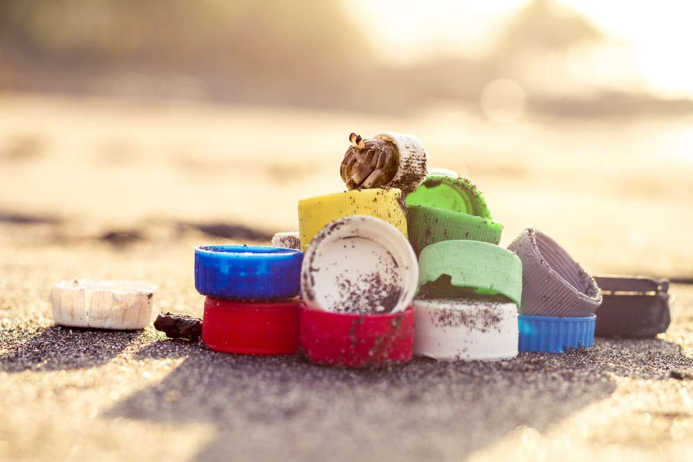 blue and red plastic containers on gray sand