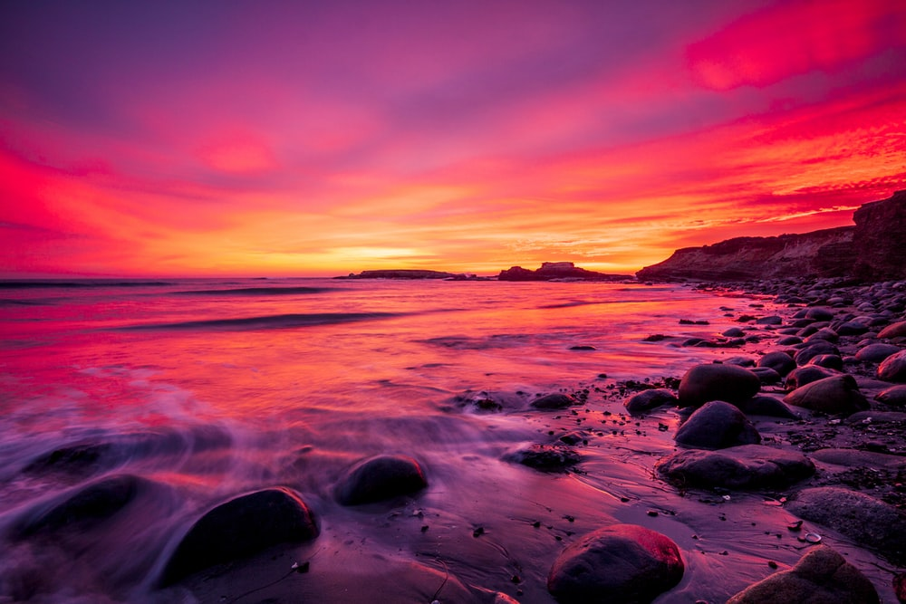 rocky shore during sunset with red sky