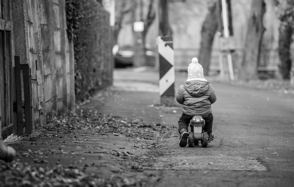 grayscale photo of child riding on bicycle