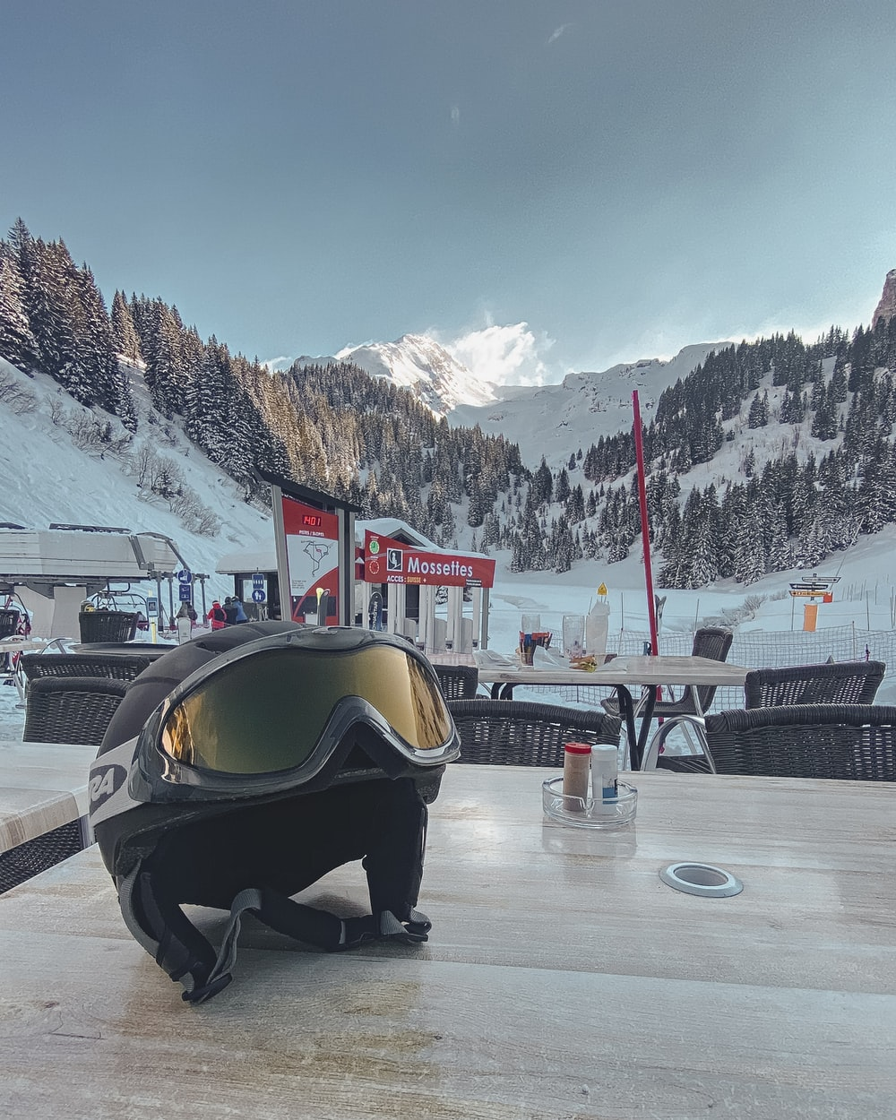 person in black jacket sitting on snow covered ground during daytime