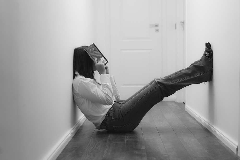 woman in white long sleeve shirt and black pants sitting on floor