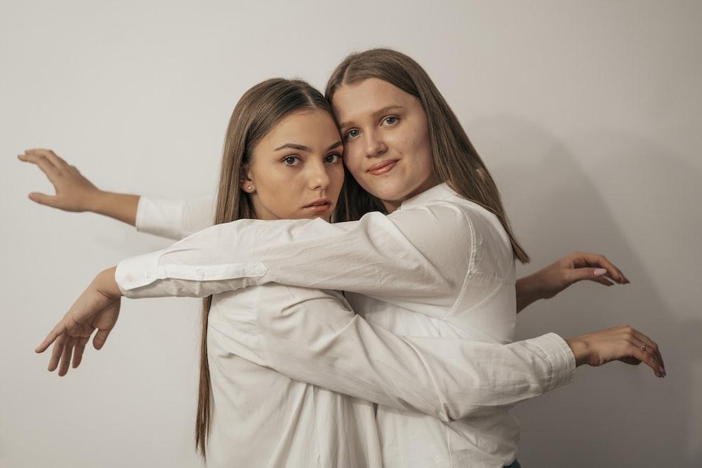 woman in white long sleeve shirt hugging woman in white long sleeve shirt