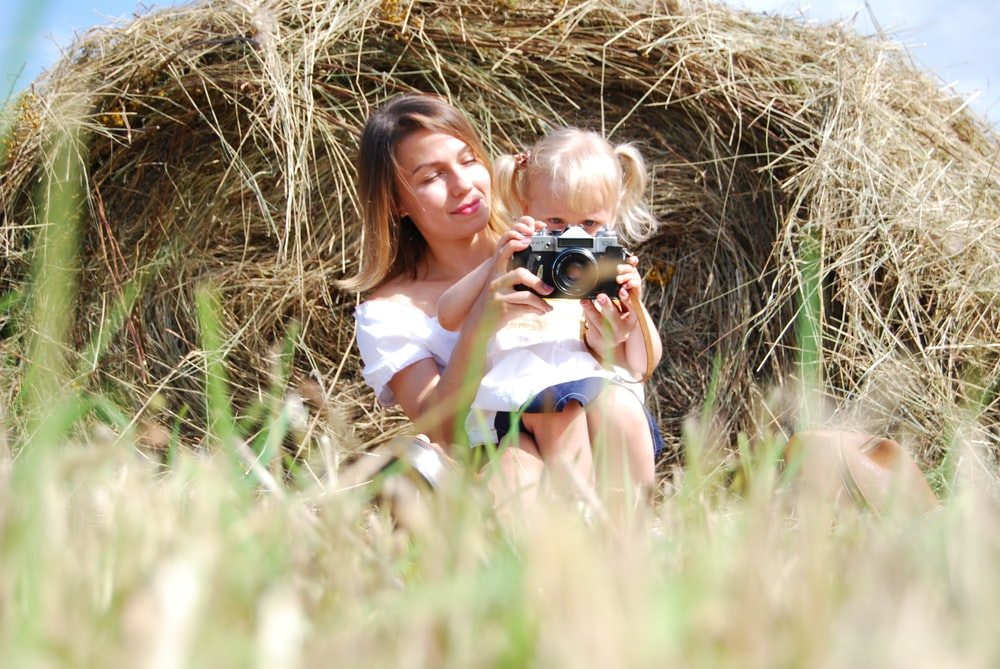 woman in white tank top holding black dslr camera sitting on brown grass field during daytime
