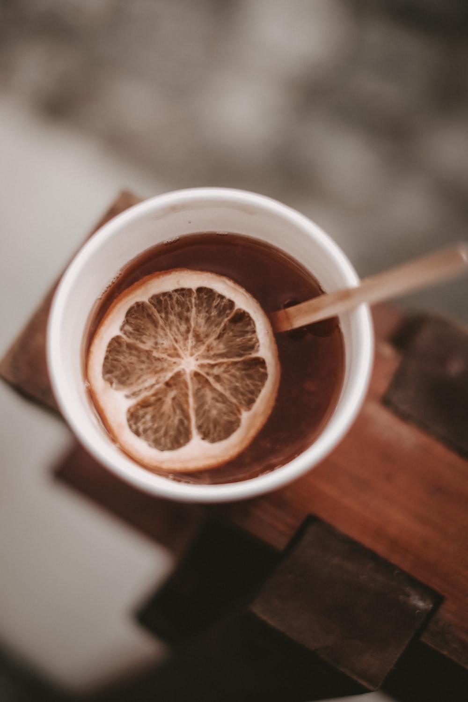 brown liquid in white ceramic mug with sliced lemon