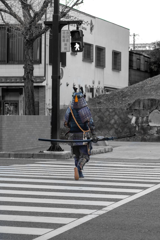 man in blue and black suit holding black rifle walking on pedestrian lane during daytime