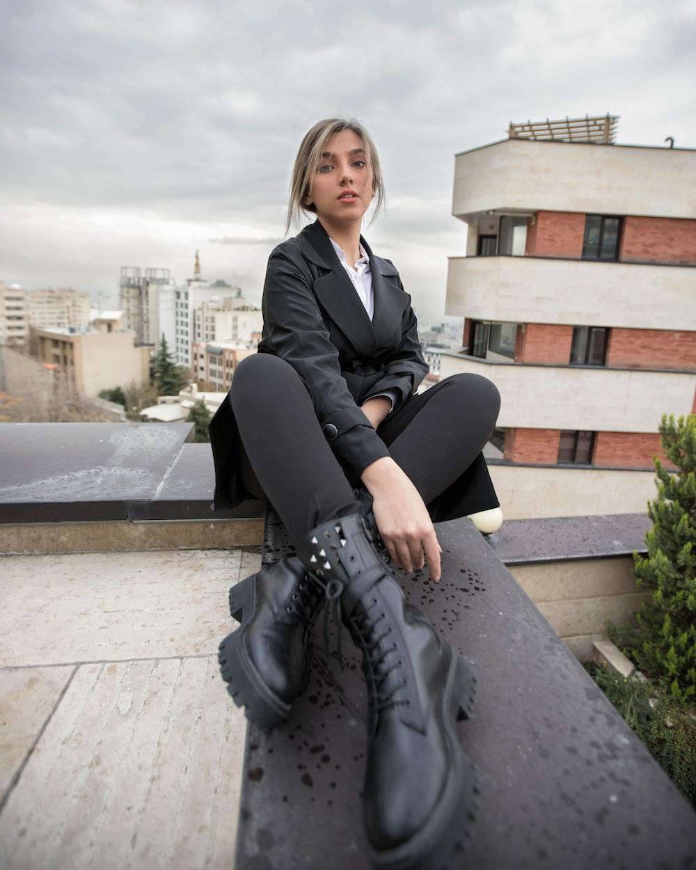 woman in black blazer sitting on concrete bench