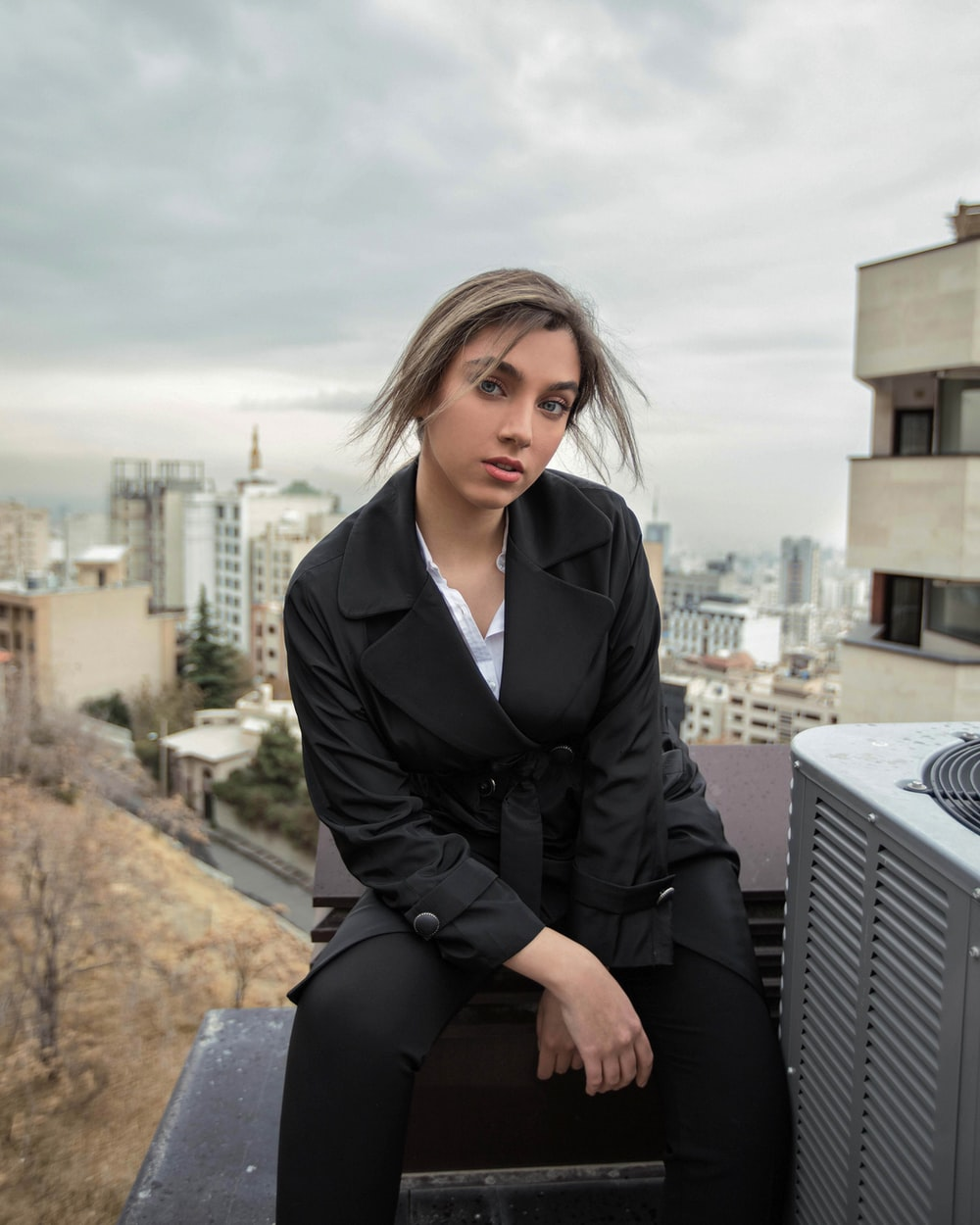 woman in black blazer sitting on concrete bench during daytime