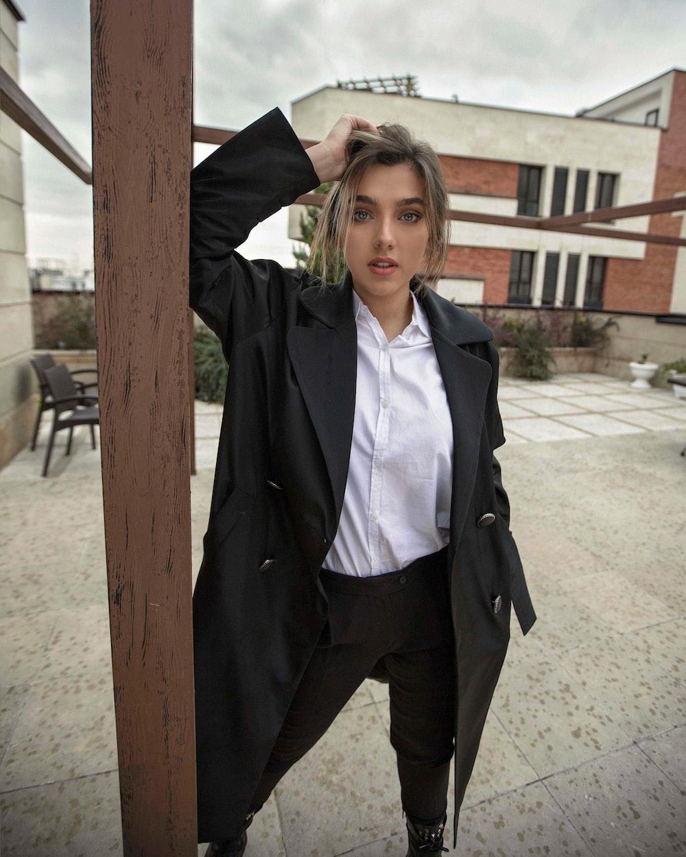 woman in black coat standing beside brown wooden post