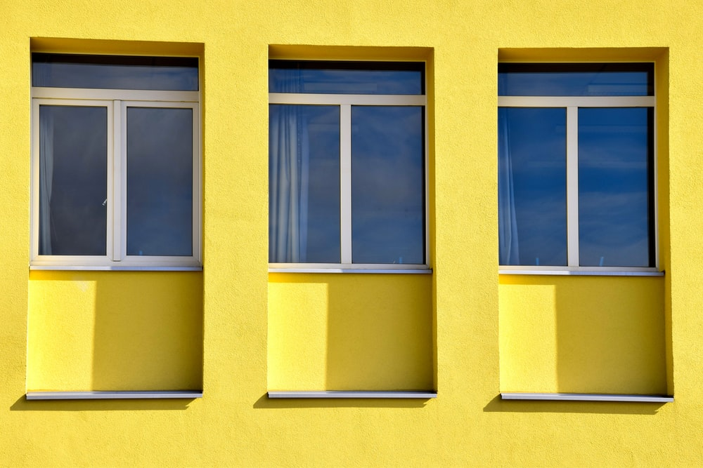 yellow concrete building with glass windows