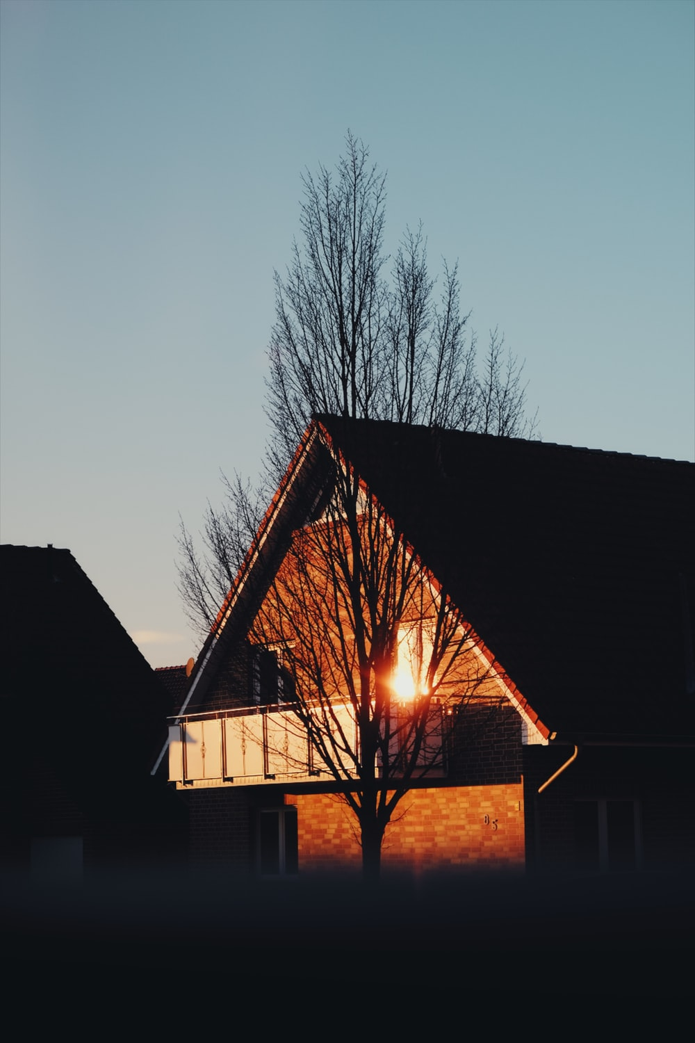 brown and white house near bare trees during sunset