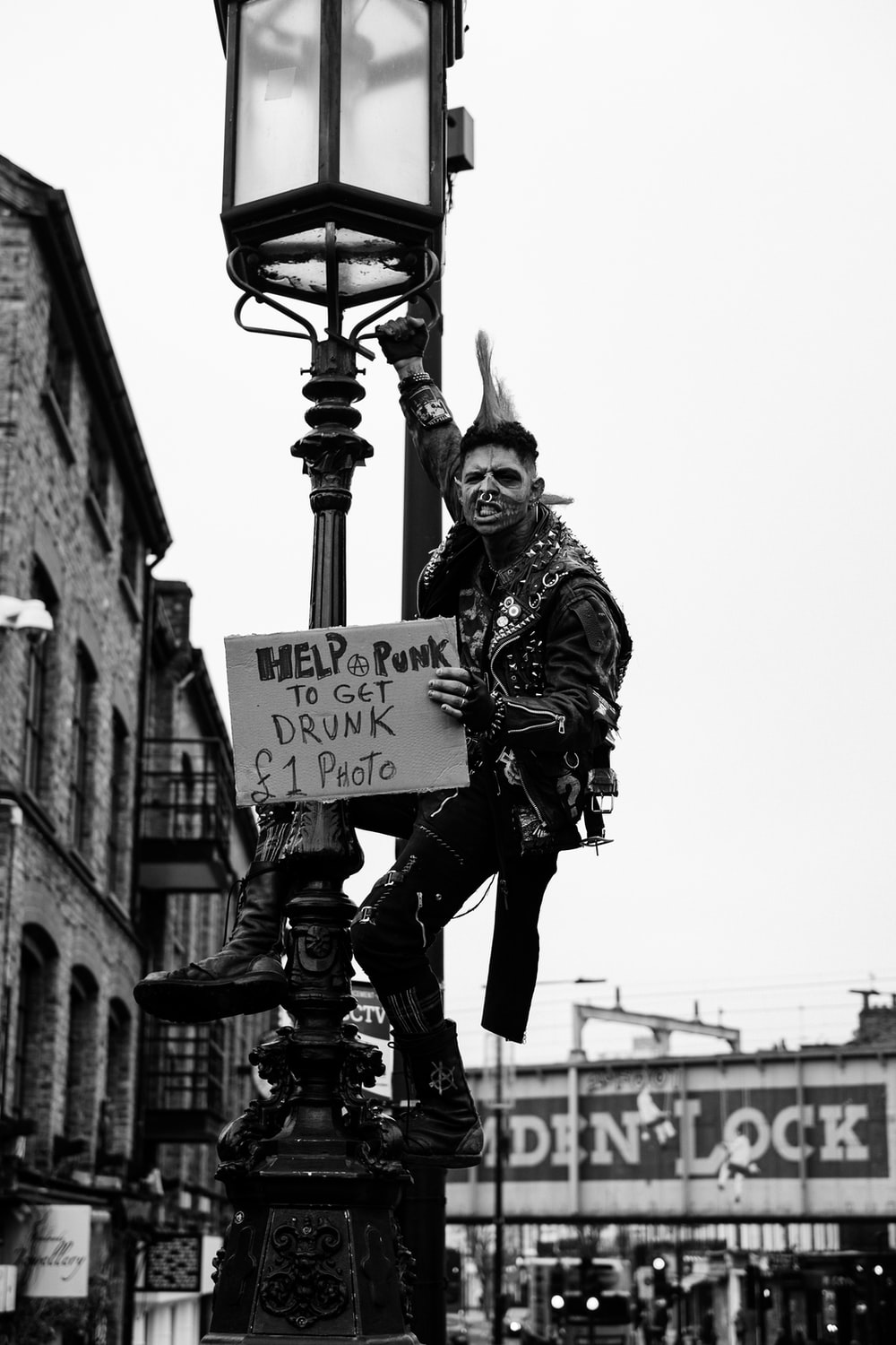 grayscale photo of man in jacket and pants holding signage