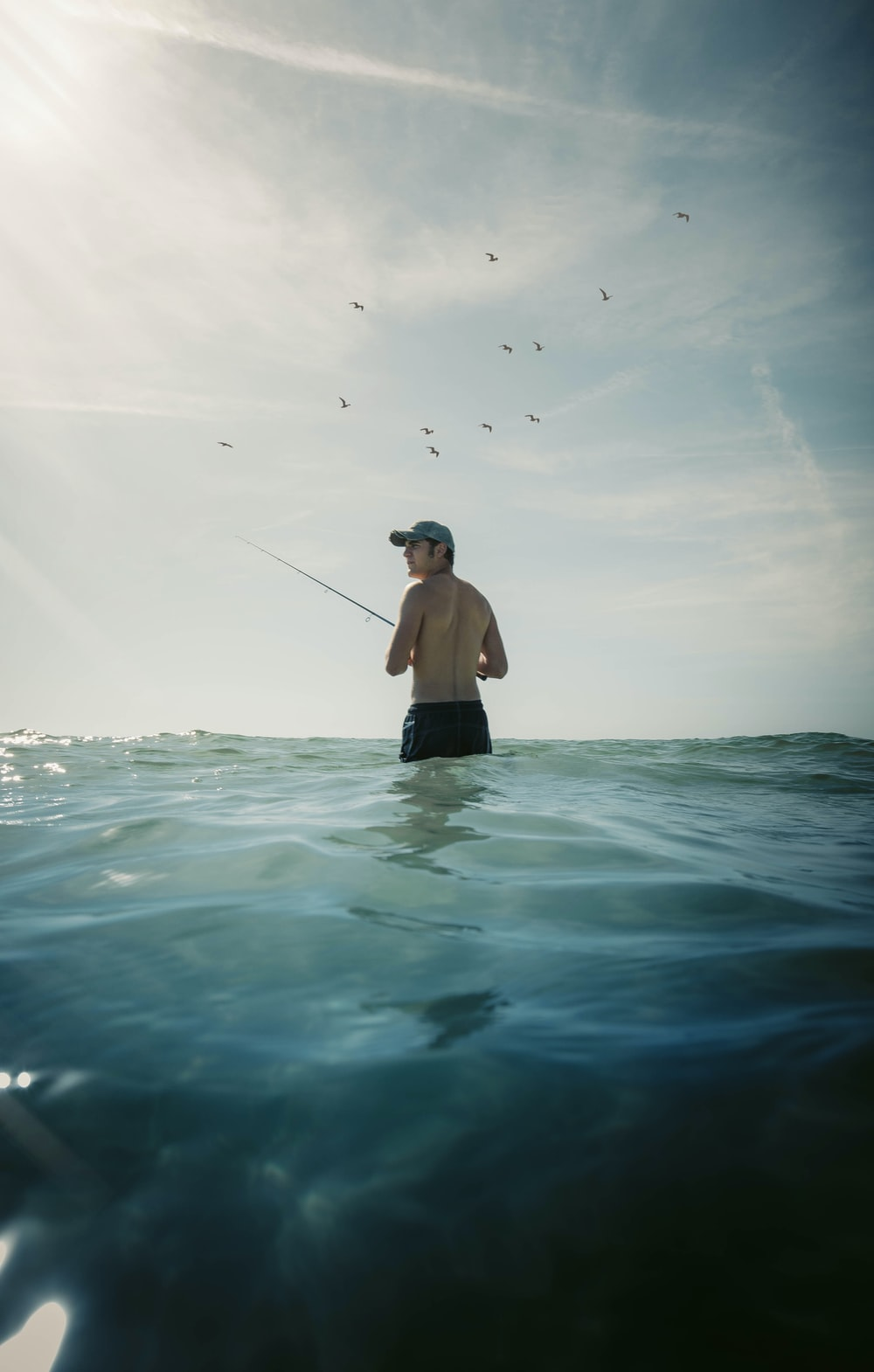 man in black shorts holding black fishing rod in water
