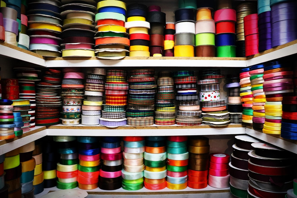 assorted color thread roll on white wooden shelf