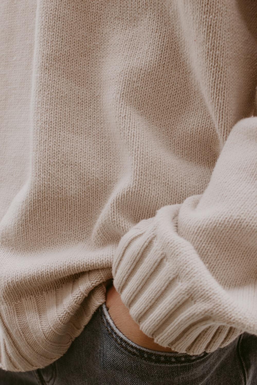 person holding white knit textile
