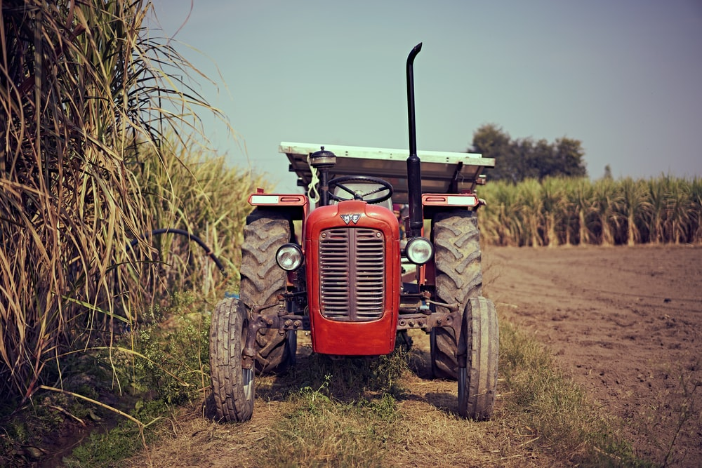 red tractor on brown grass field during daytime