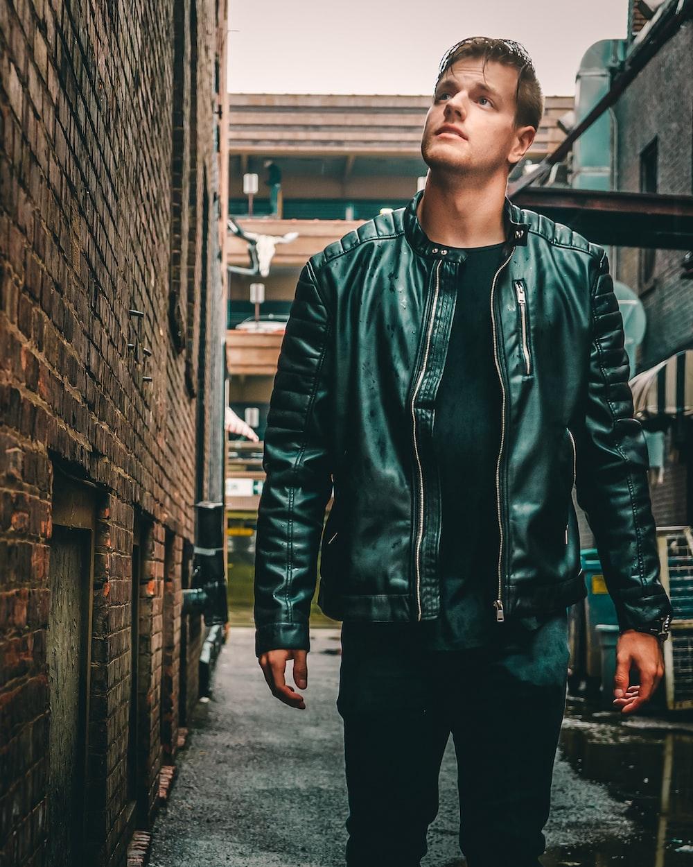 man in green zip up jacket standing beside brick wall