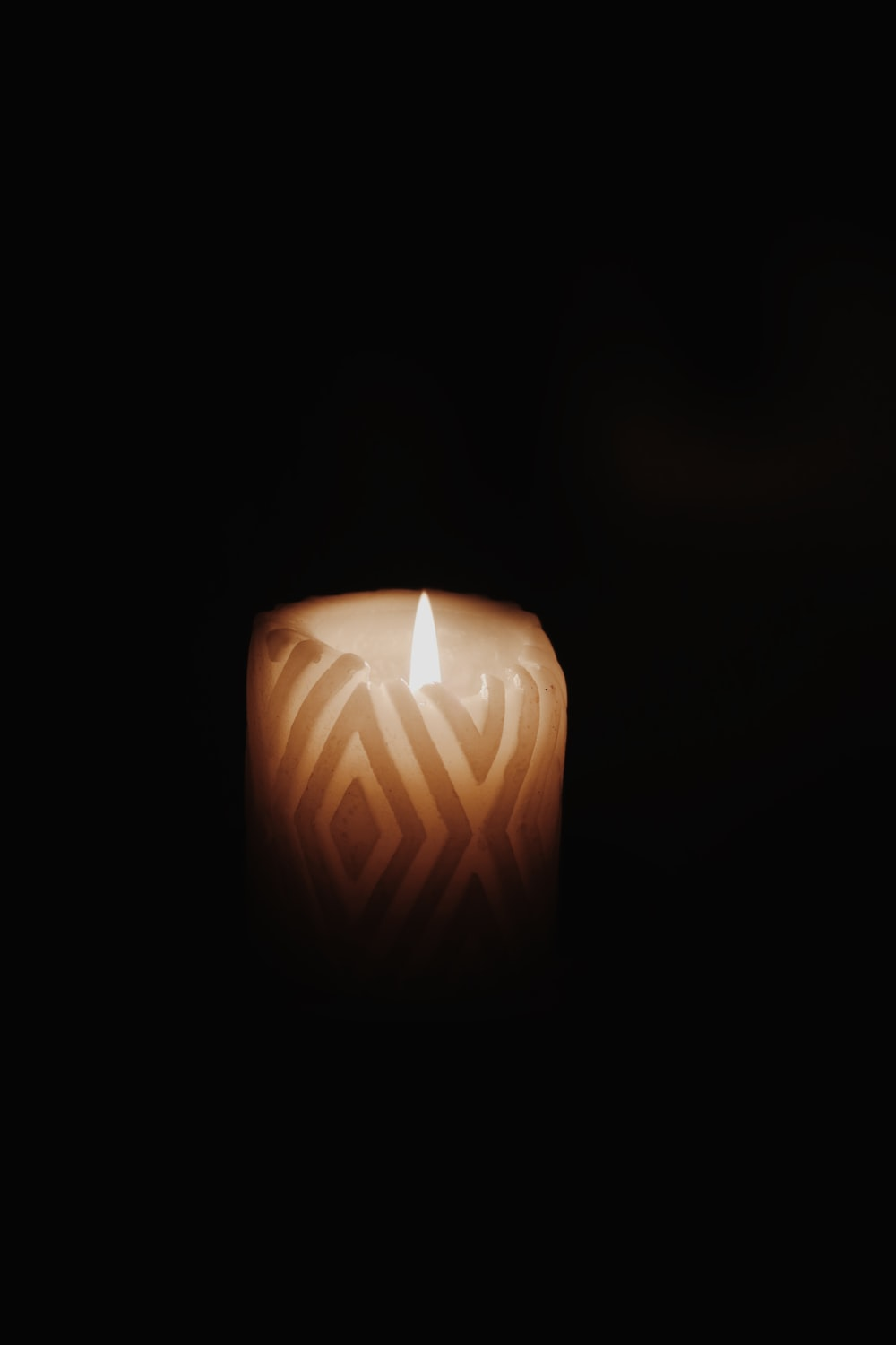 lighted candle in dark room
