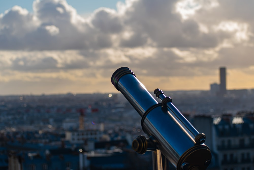 black telescope in front of city buildings during daytime