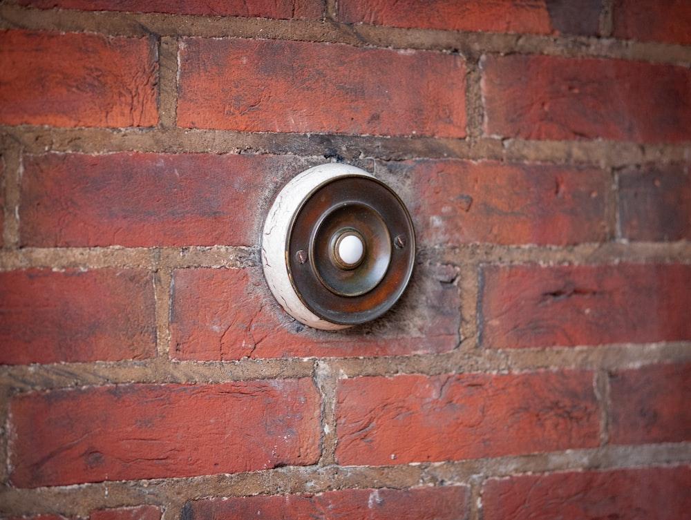 brown and black round metal on brown brick wall