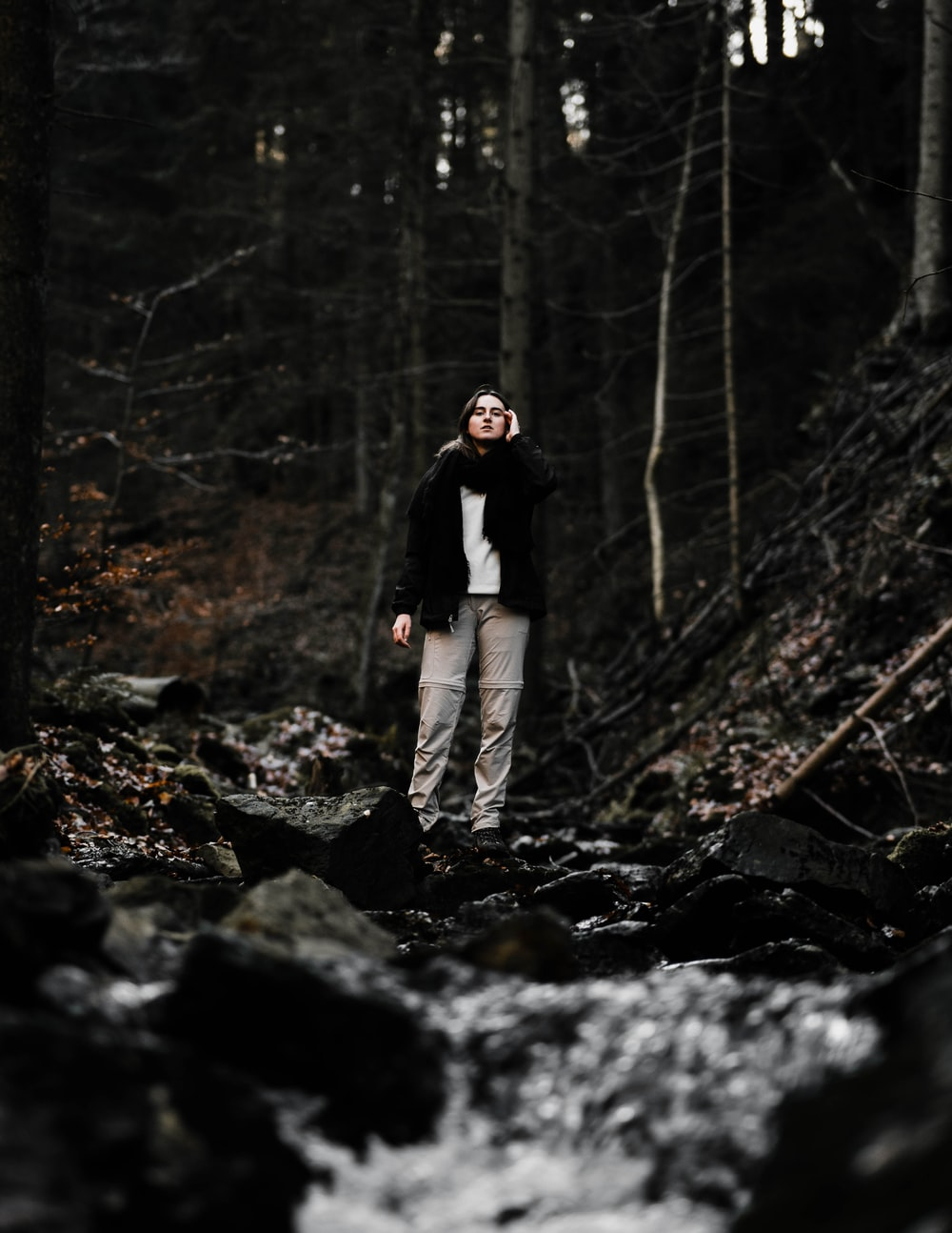 man in black jacket and gray pants standing on rocky ground surrounded by trees