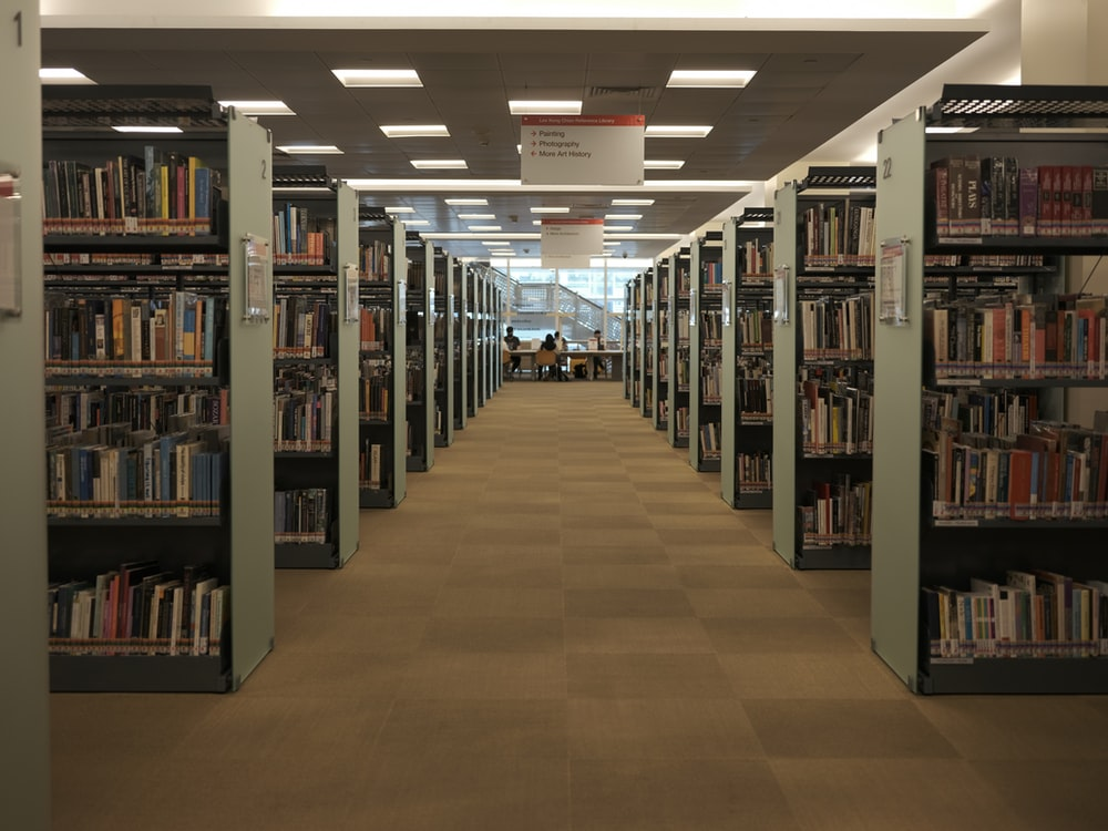brown wooden book shelves on library database pim centralization features ecommerce