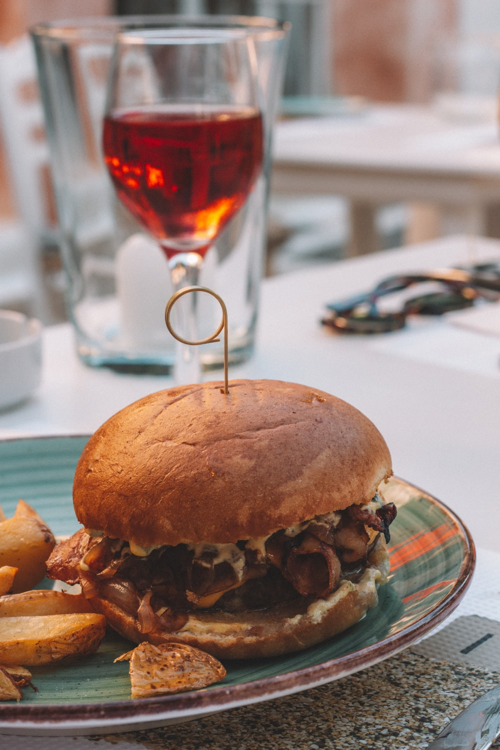 burger with fries on white table