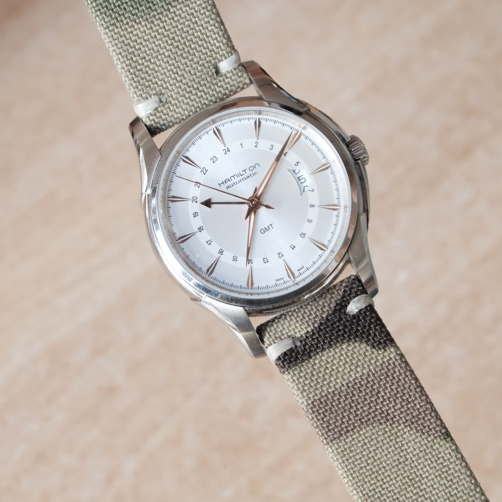 silver and white analog watch at 10 10