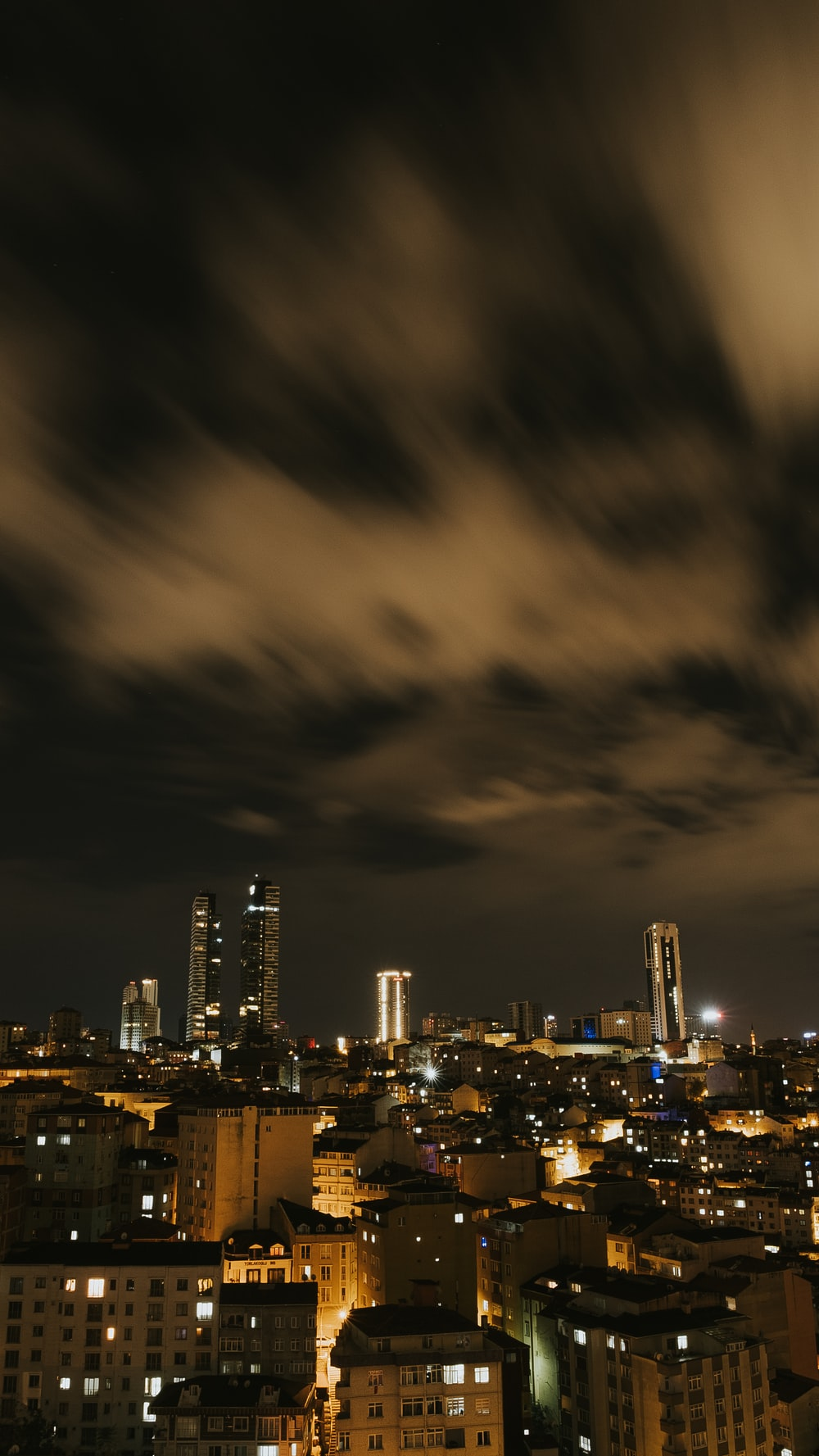 city skyline under gray clouds during night time