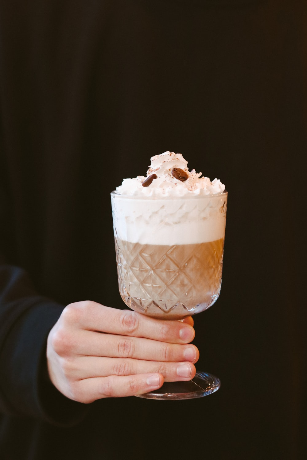 person holding ice cream in clear glass cup