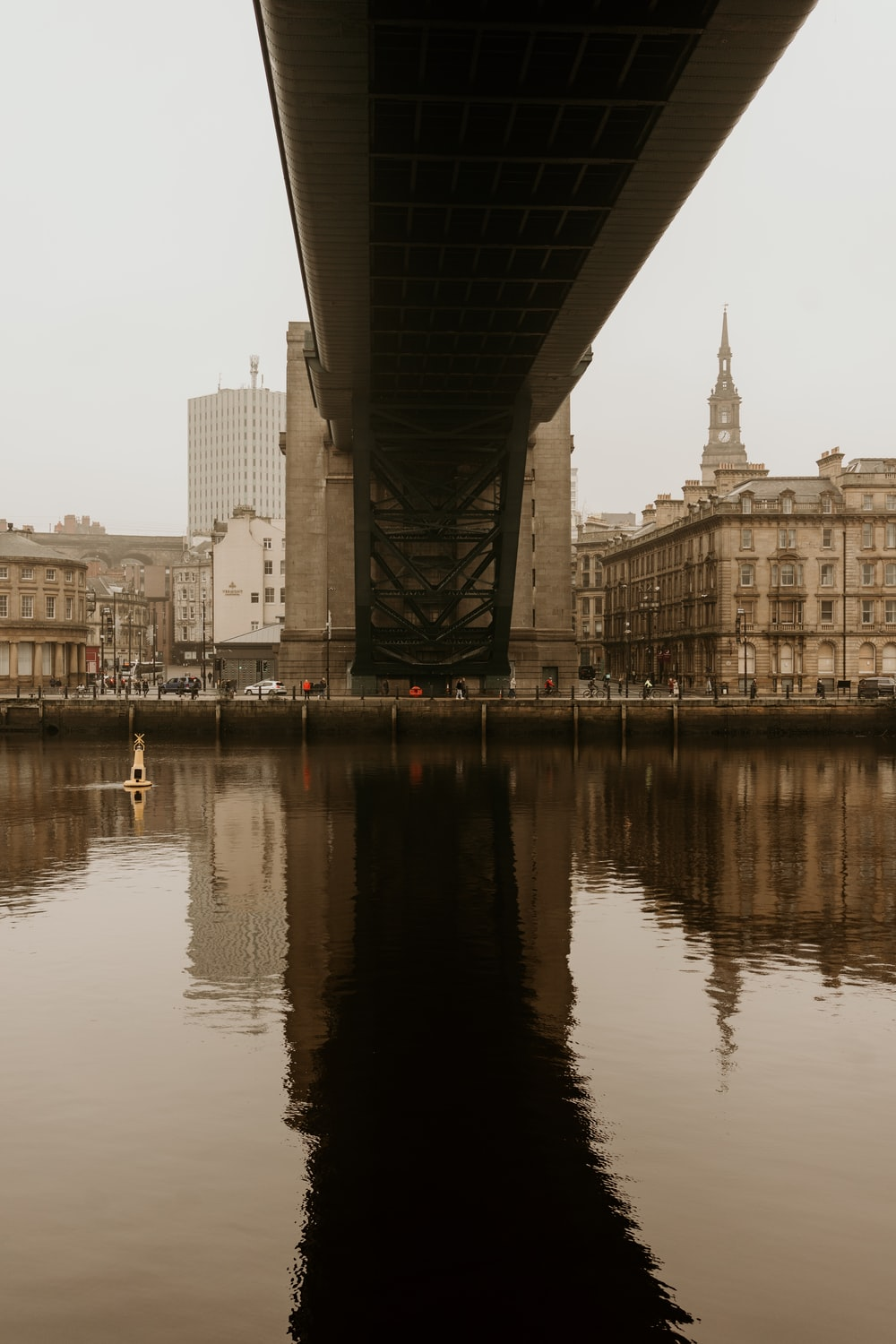 body of water near bridge and buildings during daytime