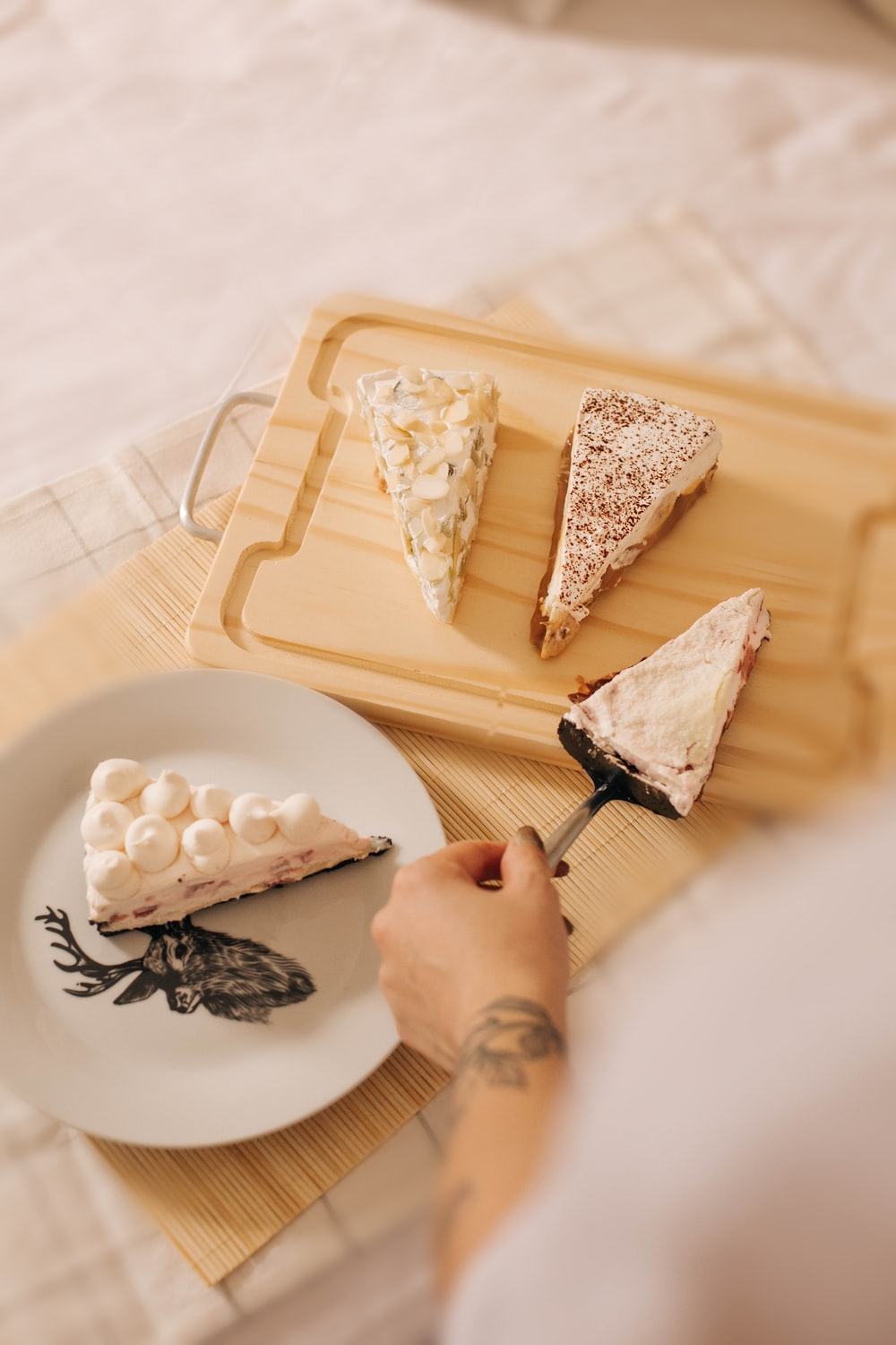 person slicing white cheese on white tray