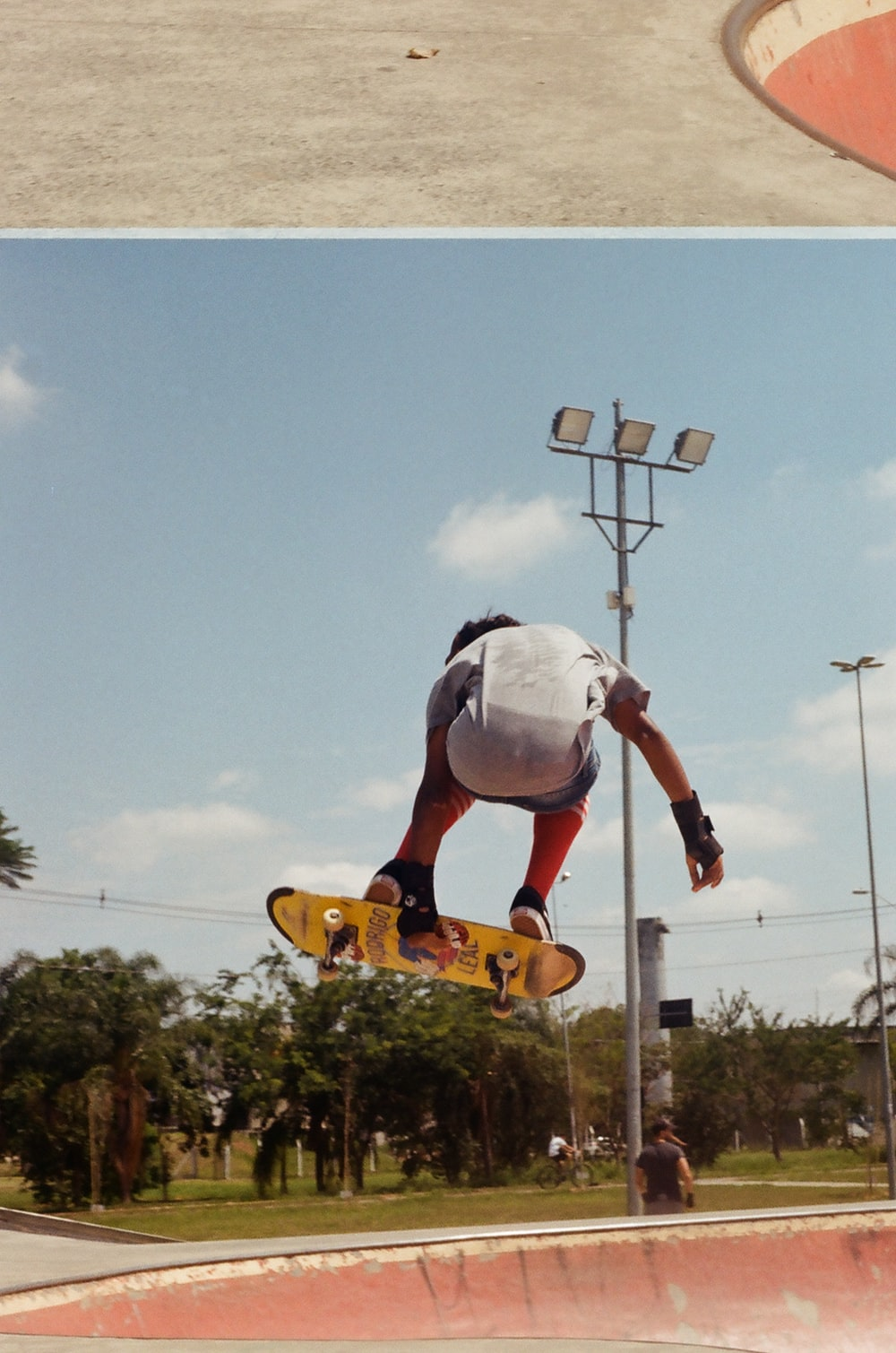 man in white helmet riding orange and white skateboard during daytime