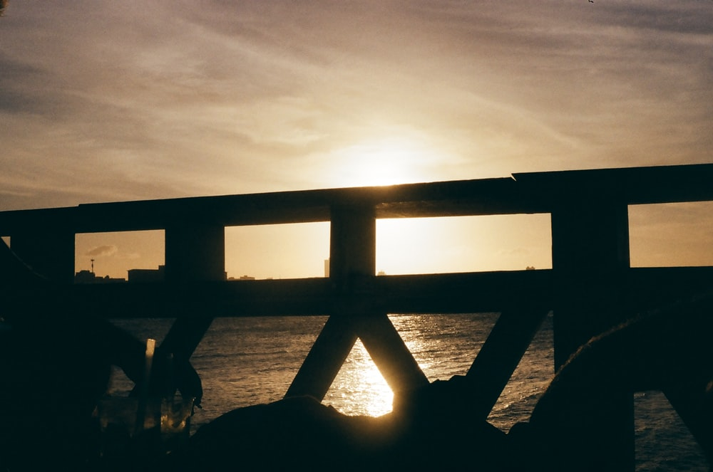 silhouette of a person sitting on a wooden dock