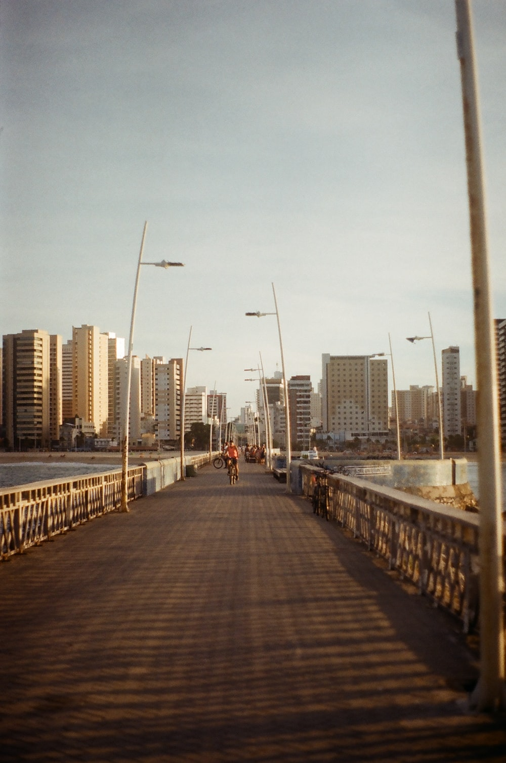 people walking on gray concrete bridge near city buildings during daytime
