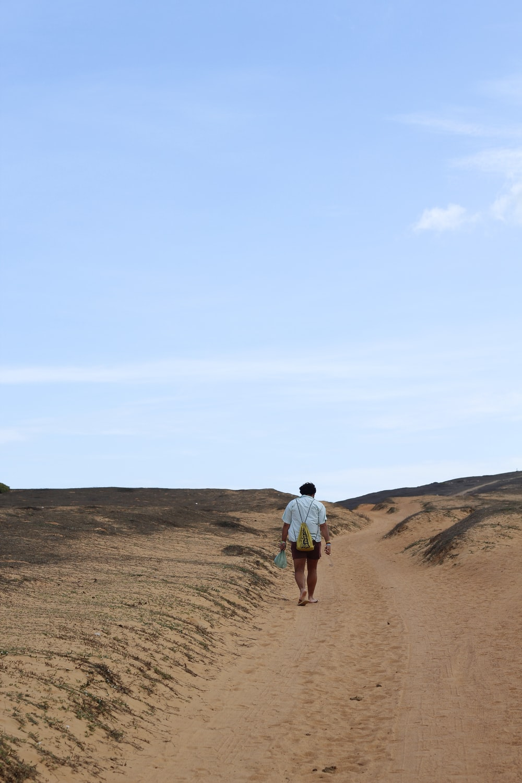 man in white t-shirt walking on brown sand during daytime