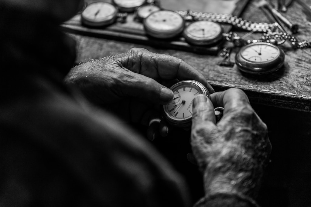 grayscale photo of person holding pocket watch
