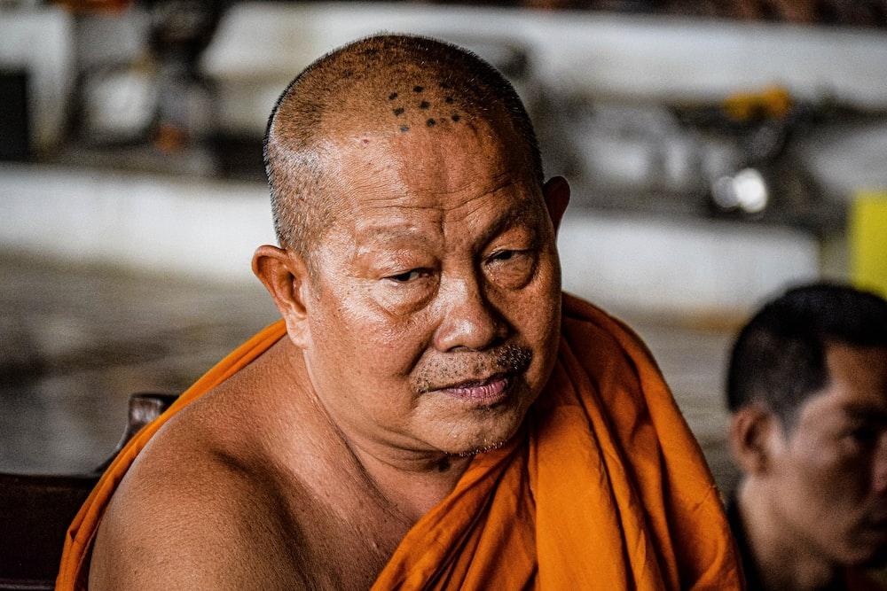 man in orange robe during daytime
