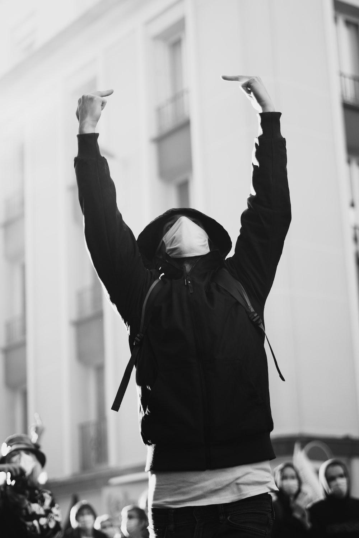 man in black jacket raising his hands