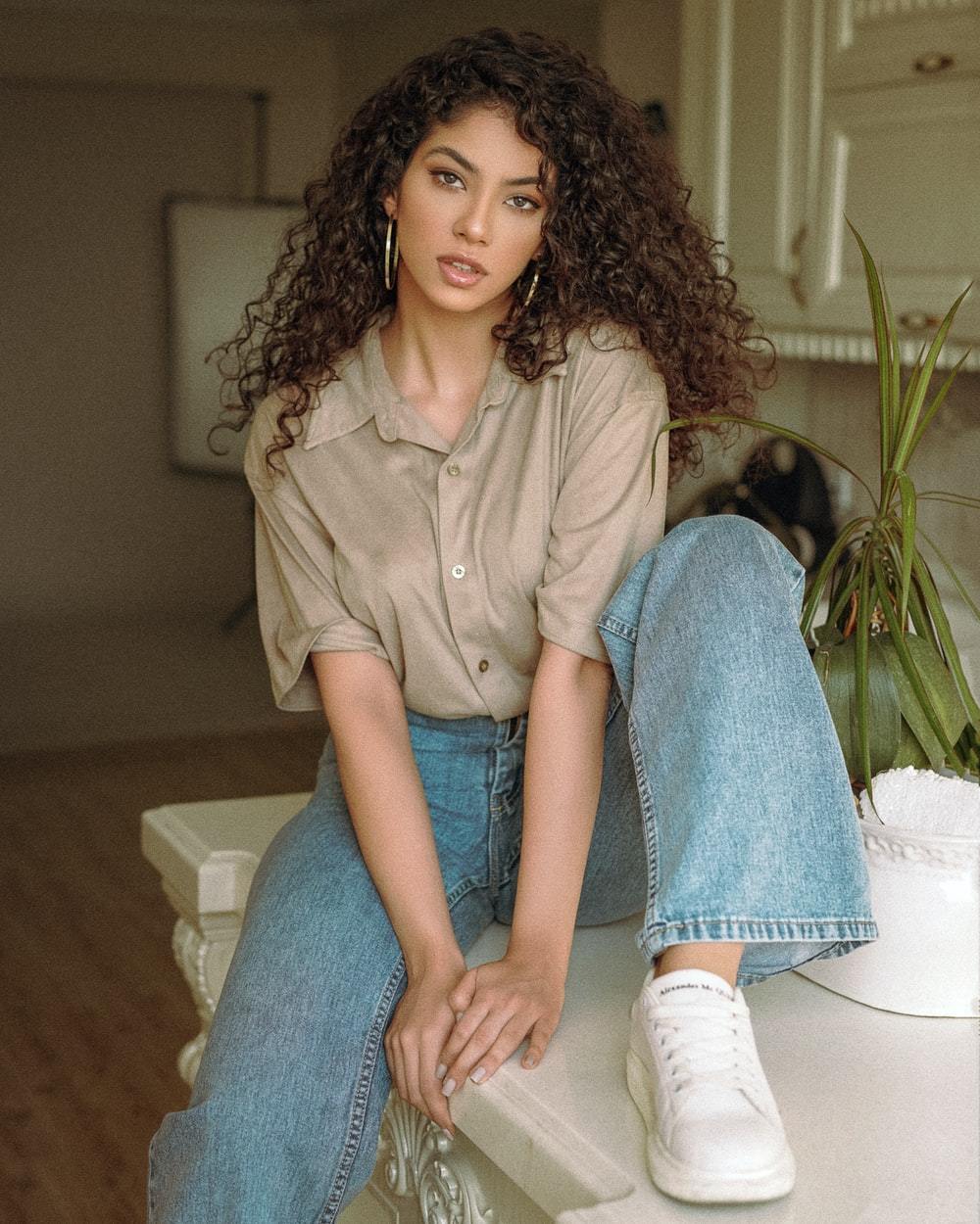woman in brown button up shirt and blue denim jeans sitting on white couch
