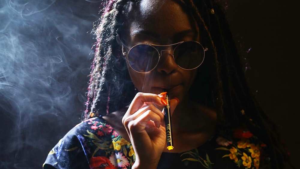 woman in black framed sunglasses smoking cigarette