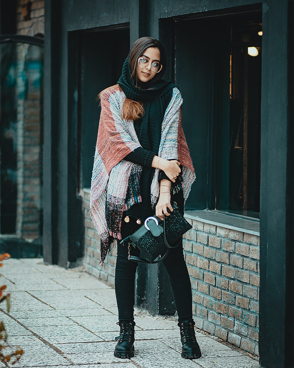 woman in black pants and red scarf standing on sidewalk during daytime