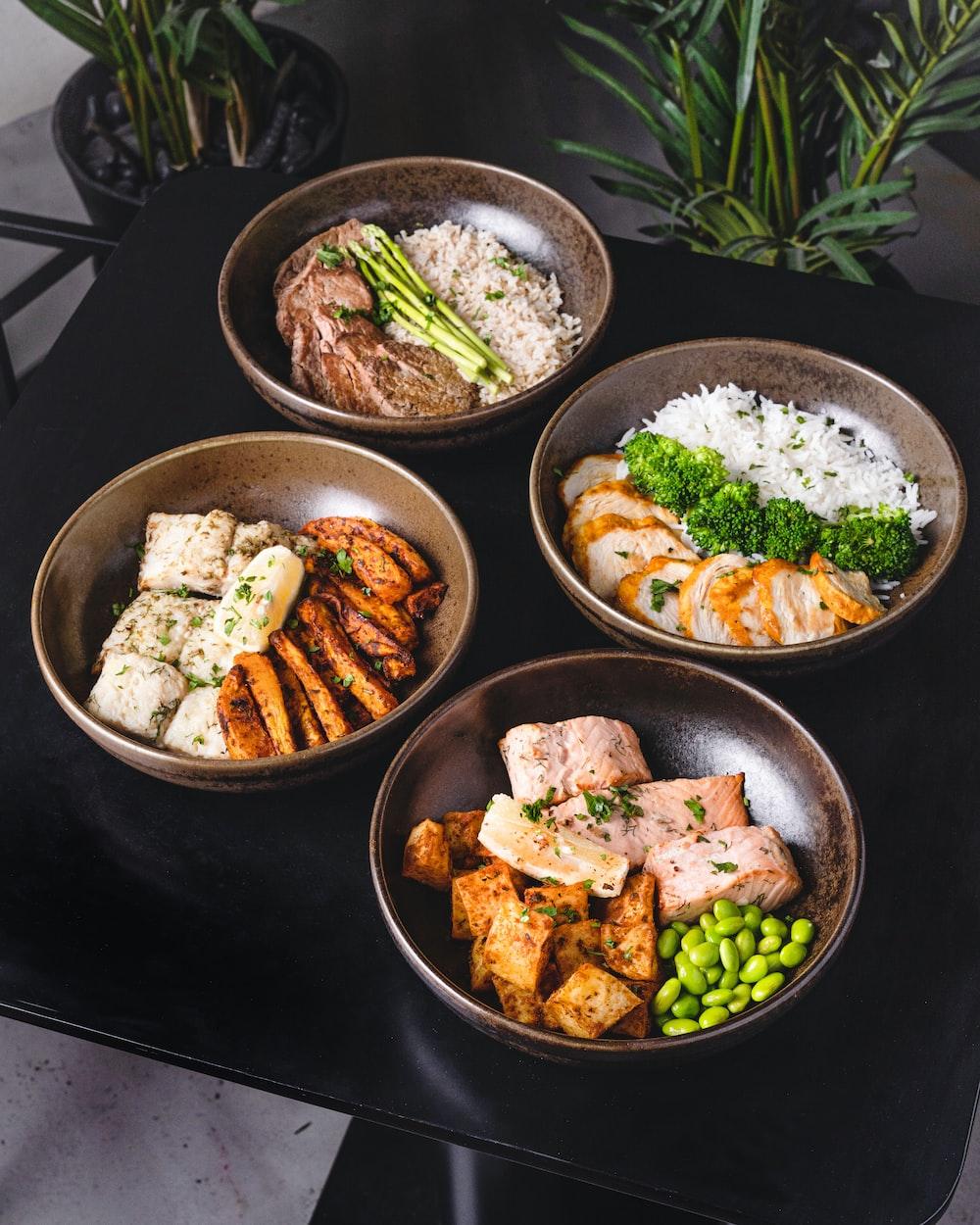 cooked food on black ceramic bowls