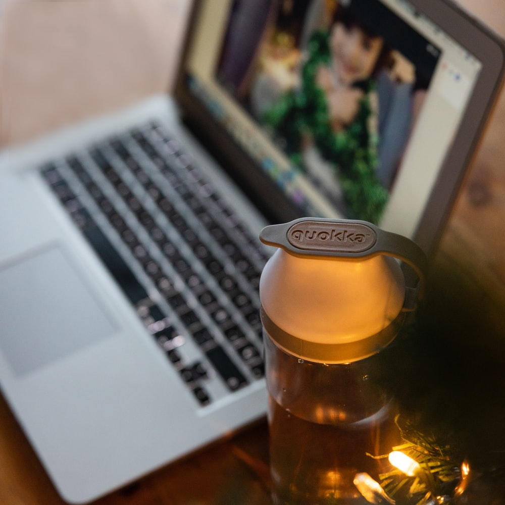 clear glass bottle beside macbook pro