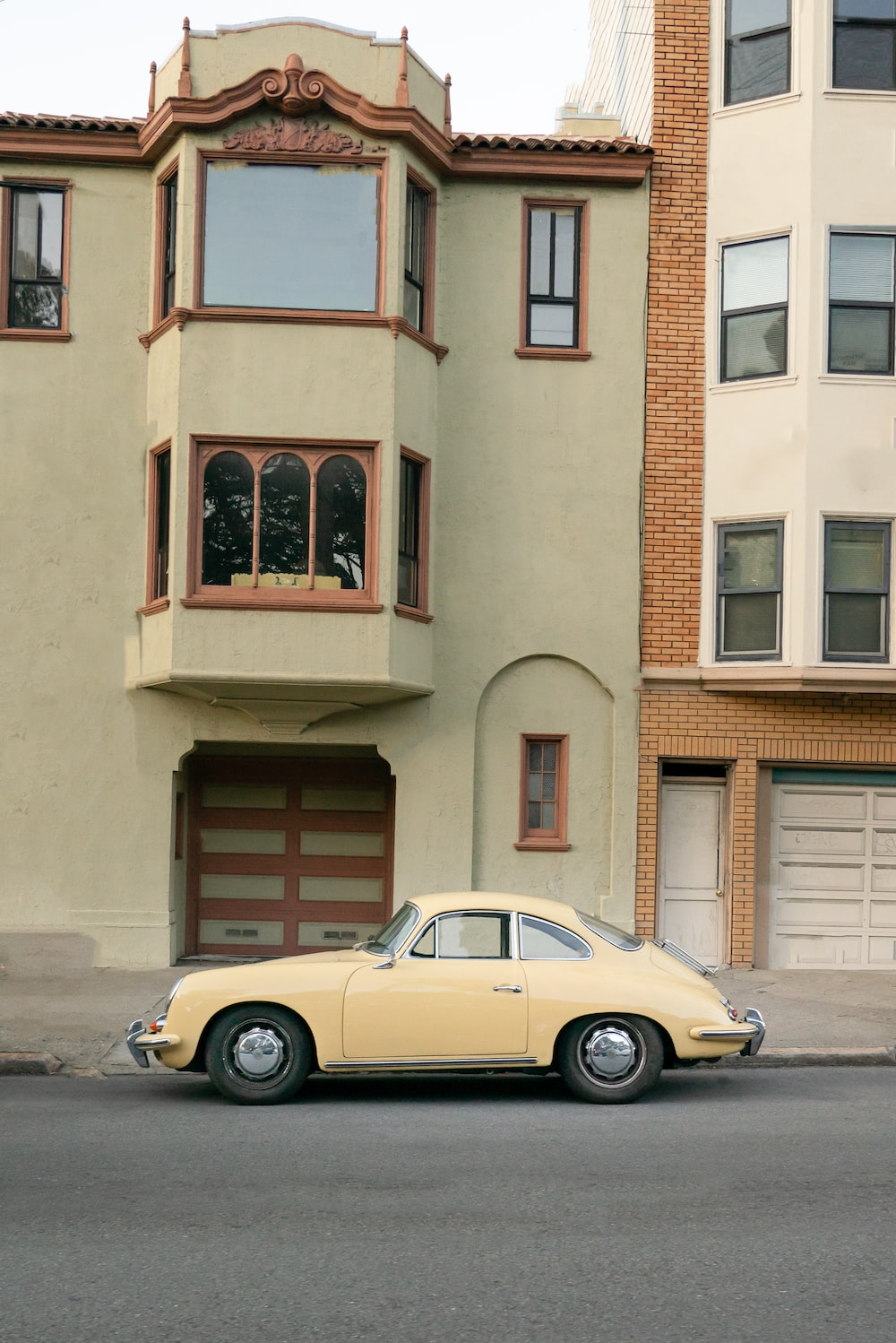 yellow coupe parked beside brown concrete building during daytime