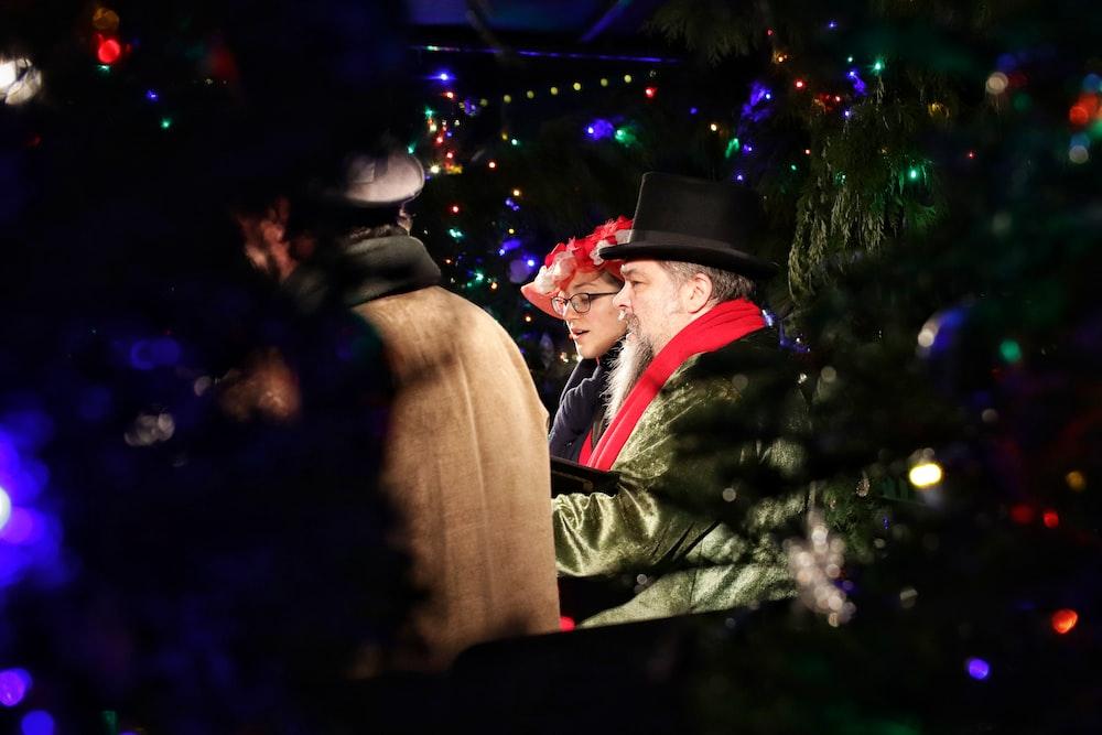 man and woman standing near christmas tree