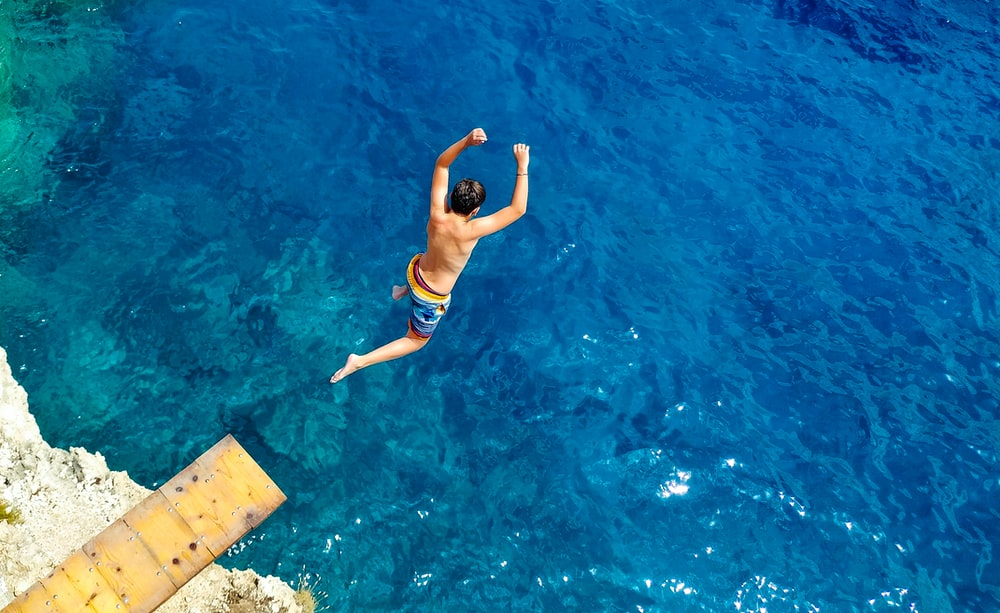 man in blue shorts jumping on water during daytime