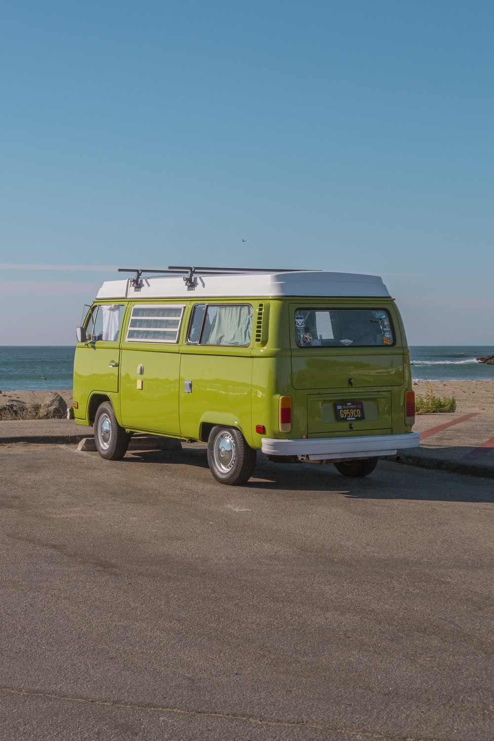 green volkswagen t-2 on brown soil near body of water during daytime