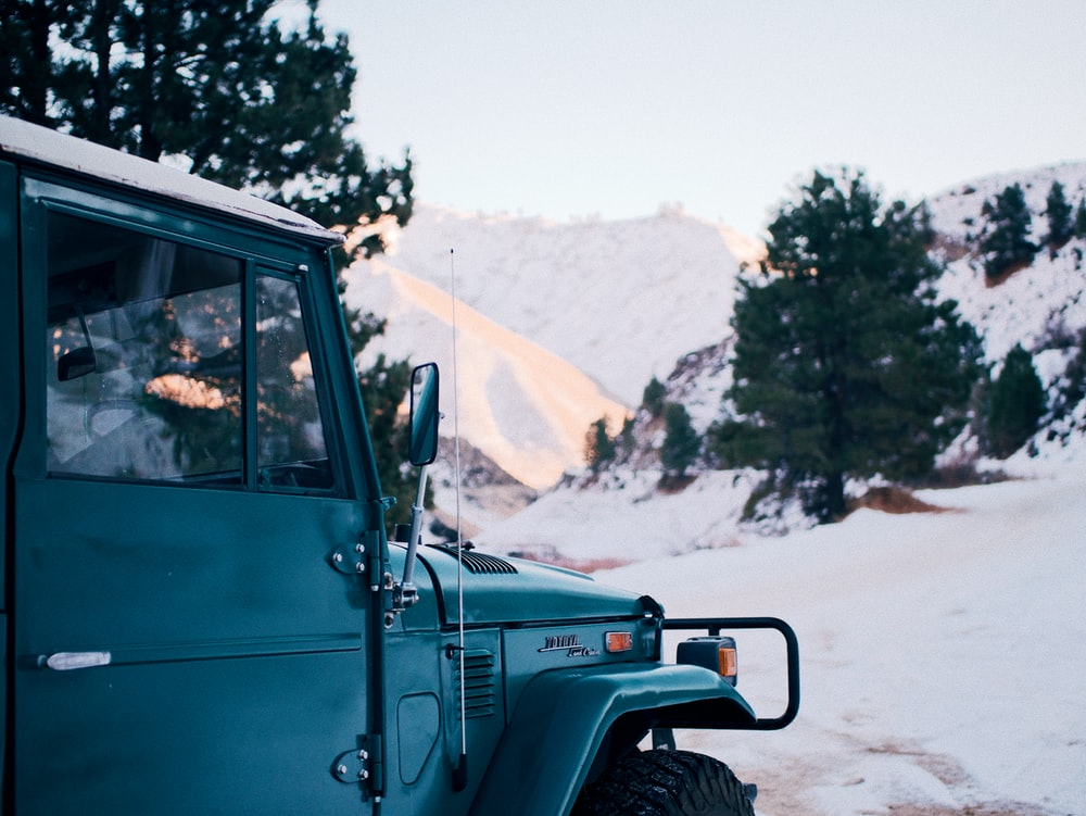 green jeep wrangler on snow covered field during daytime