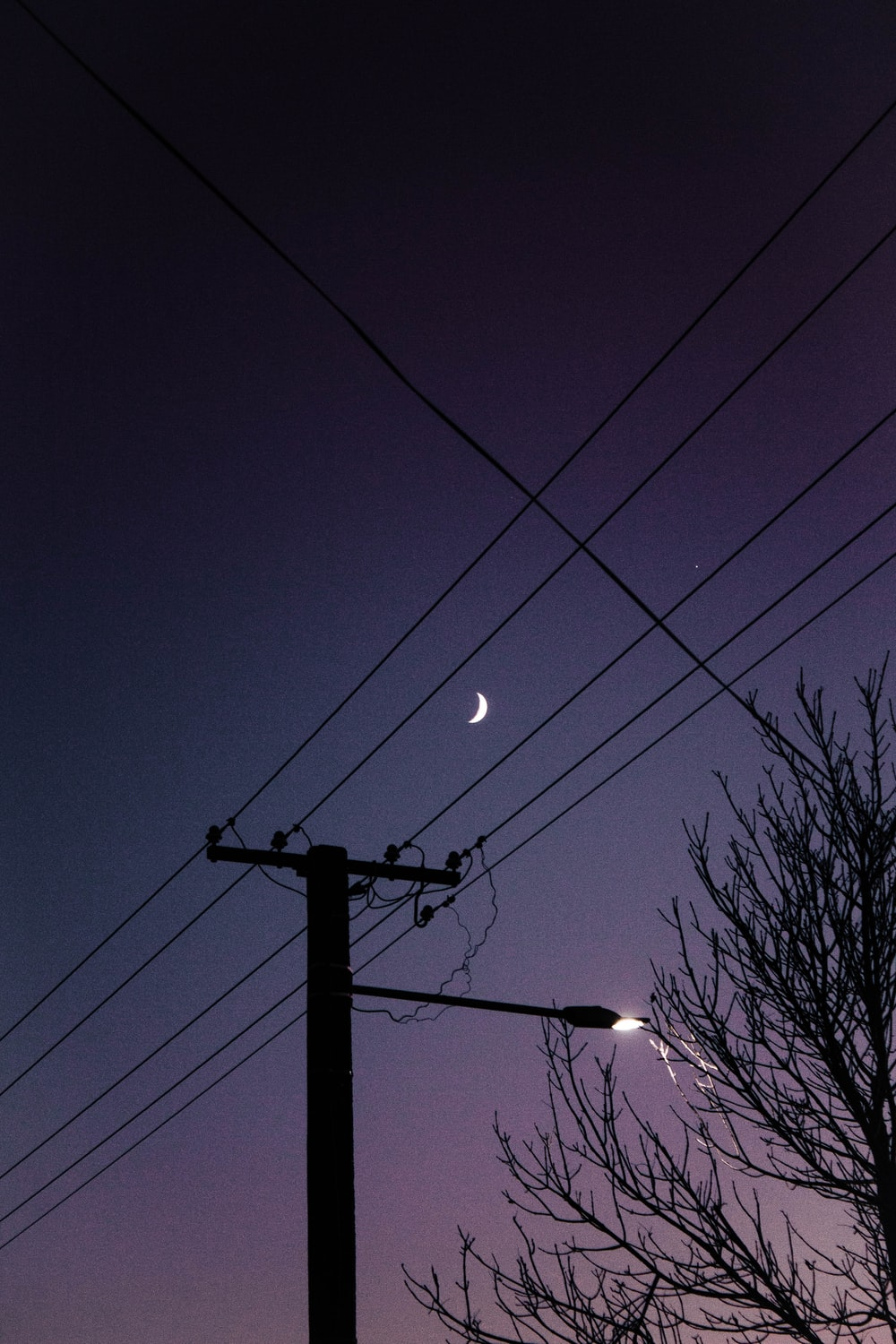 black electric post under blue sky during night time