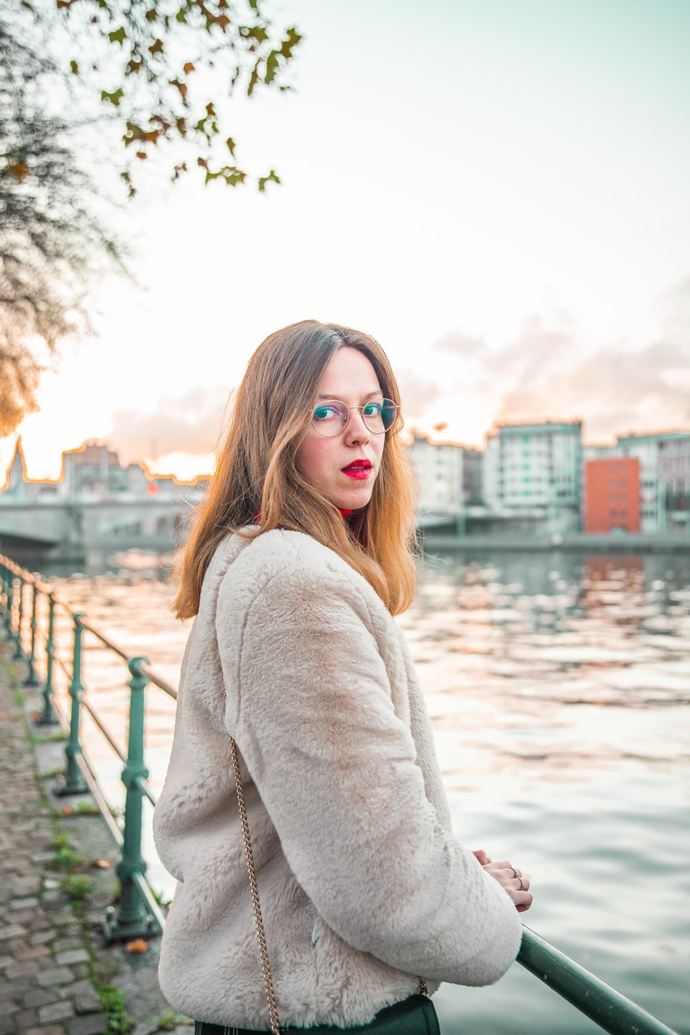 woman in white sweater standing near body of water during daytime